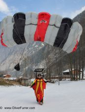 BASE jumper under canopy landed on snow