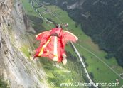 BASE jumper exit from cliff down the valley