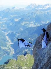 Wingsuit BASE jumpers are exiting from a cliff