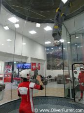indoor skydiver is head over flying down